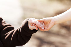 Älteres Frauenhändchenhalten mit jungem Wärter Lizenzfreies Stockbild