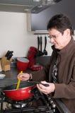 Älteres Frauenkochen stockbild