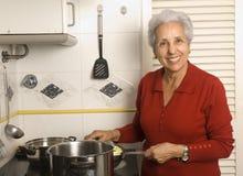 Älteres Frauenkochen Stockfotos