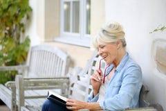 Älteres Frauenlesebuchgenießen Lizenzfreies Stockbild