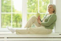 Älteres Frauenporträt mit Tasse Tee Stockbild