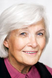 Älteres Frauenportrait mit violetter Bluse Stockfotos