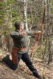Älteres Frauenschießen mit einem traditionellen Bogen Stockfotos