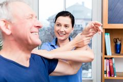 Älteres geduldiges Handelnschultertraining unter Unterstützung des Therapeuten Stockfotos