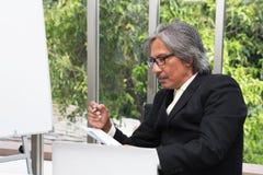 Älteres Geschäft, das Dokumente im Konferenzzimmer analysiert Geschäftsmann stockfoto