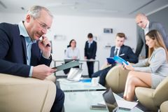 Älteres Geschäftsmann-Reading Document On-Klemmbrett im Büro lizenzfreie stockfotos