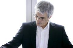 Älteres graues Haar des Geschäftsmannes, das unten schaut Lizenzfreie Stockbilder
