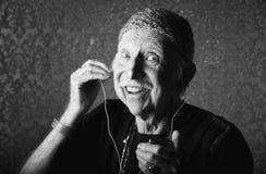Älteres Hiptser, das zu Handaudioeinheit hört Lizenzfreie Stockbilder