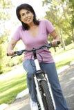 Älteres hispanisches Frauen-Reitfahrrad im Park Lizenzfreie Stockfotos