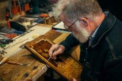 Älteres Holz, das Fachmann während der Arbeit schnitzt Stockbild