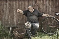 Älteres ländliches Sitzen auf einer Bank am Sommertag und Zeigen auf irgendwo Stockfoto