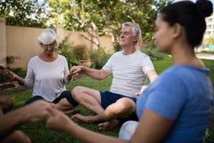 Älteres Leutehändchenhalten und Meditieren mit Trainer Lizenzfreies Stockfoto