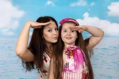 Älteres Mädchen und ihre jüngere Schwester auf Seehintergrund Lizenzfreies Stockfoto