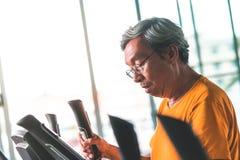 Älteres männliches Ausarbeiten auf Eignungsmaschine für gesundes Konzept des Ältesten lizenzfreies stockbild