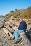 Älteres männliches Sitzen auf Strand-Treibholz lizenzfreie stockbilder