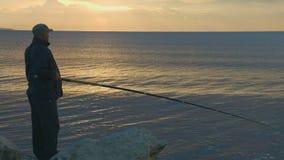 Älteres Mannfischen mit Stange von einem felsigen Ozeanufer, aktiver Rest, magische Stunde stock video footage