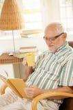 Älteres Mannlesebuch und haben Tee. Stockfoto