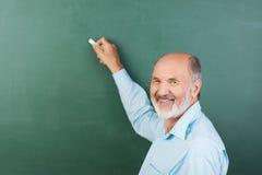 Älteres Mannschreiben auf einer leeren Tafel Stockfotografie