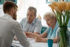 Älteres Paar konsultiert ein Mittel lizenzfreies stockbild