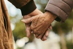 Älteres Paarhändchenhalten und -c$gehen lizenzfreie stockfotos