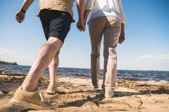 Älteres Paarhändchenhalten und Gehen auf sandigen Strand stockfotos