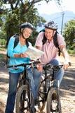 Älteres Paarreiten fährt rad, eine Karte betrachtend Stockbild