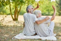 Älteres Paarsitzen entspannt und Wellenartig bewegen Lizenzfreies Stockbild