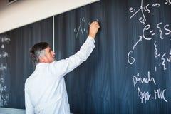 Älteres Professorschreiben auf dem Vorstand Stockfotos