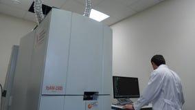 Älteres researche, das einen Computer im Labor beim Arbeiten an einem Experiment rusing ist lizenzfreies stockbild