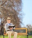 Älteres Sitzen auf Bank- und Lesebuch im Park Lizenzfreies Stockbild
