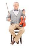Älteres Sitzen auf einem Stuhl und einer Holding eine Violine Lizenzfreies Stockfoto
