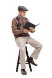 Älteres Sitzen auf einem Stuhl und einer Lesung ein Buch Stockfotografie