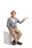 Älteres Sitzen auf einem Würfel und Gestikulieren mit seiner Hand Stockfoto