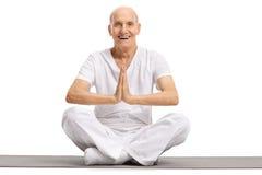 Älteres Sitzen auf einer Übungsmatte und einem übenden Yoga Stockfotografie