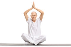 Älteres Sitzen auf einer Übungsmatte und Meditieren Lizenzfreie Stockbilder