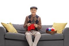 Älteres Sitzen auf einer Couch und einem Stricken Stockfoto