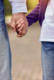 Älteres und junges Händchenhaltengehen Lizenzfreie Stockfotos