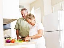 Älteres verheiratetes Paar, das Abendessen kocht Stockbild
