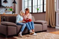 Älteres weibliches Sitzen auf Sofa mit ihrer Jungerwachsentochter lizenzfreies stockfoto