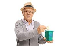 Älteres werfendes Stück Abfall in einem kleinen Wiederverwertungsbehälter Stockfoto
