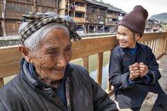 Älteste chinesische ländliche Frau, die auf Bank in der ländlichen Straße stillsteht Stockbilder