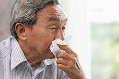 Ältestes des alten Mannes erhalten krankem Abwischen den Nasenrotz von der Grippe und von der laufenden Nase Stockfoto