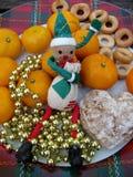 Älva, mandariner, ljust rödbrun kaka, baglar och xmas-garnering Fotografering för Bildbyråer