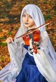 Älva med en fiol i höstskogen Fotografering för Bildbyråer