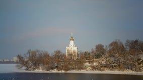 Änder simmar i den djupfrysta floden på bakgrunden av kyrkan på ön lager videofilmer