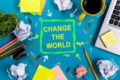 Ändern Sie die Welt Bürotischschreibtisch mit Versorgungen, weißer leerer Notizblock, Schale, Stift, PC, zerknitterte Papier, Blu Lizenzfreies Stockbild