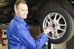 Ändernde Gummireifen des Mannes in der Garage Lizenzfreie Stockfotos