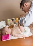 Ändernde Windel des Vaters des entzückenden Babys Lizenzfreie Stockbilder