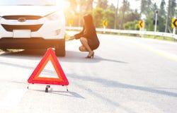 Ändernder Reifen des Geschäftsfrau-Fahrers Stockfoto