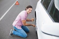 Änderndes Rad des Mannes nach einem Autozusammenbruch lizenzfreie stockbilder
